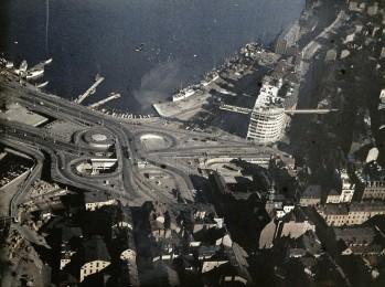 1930-TALSLÖSNING. Gustaf W:son Cronquists flygfoto från 1936 visar Slussens klöverblad i dess blomningstid. Den omfattande betongkonstruktionen, byggd för vänstertrafik, har aldrig utnyttjas till sin fulla kapacitet. Bild från Stockholmskällan.