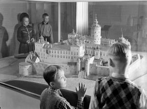 SE OCH RÖRA? Modeller som är gjorda för att vidröras och ge en taktil upplevelse av existerande eller historiska byggnader kan förhöja tillgängligheten. Här skolbarn i ett äldre Stockholm, som betraktar ett ännu äldre: en modell av slottet Tre Kronor. (Stadsmuseet/Stockholmskällan.)